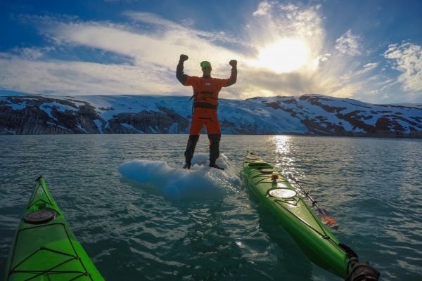 guided tours at svartisen glacier with kayaks, stand on top of a floating iceberg